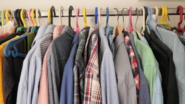 vídeos de stock e filmes b-roll de closet with men's and women's clothes - closet