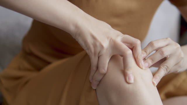 close-up 4k resolution shot of asian woman hand massaging on his knee pain and feeling bad in the living room at home . massage therapy from playing and injury from sport. - cramp stock videos & royalty-free footage