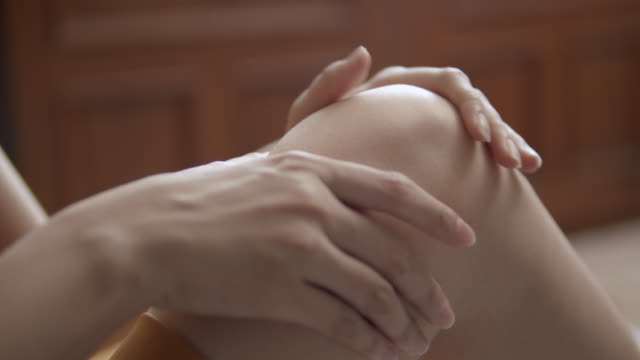 close-up 4k resolution shot of asian woman hand massaging on his knee pain and feeling bad in the living room at home . massage therapy from playing and injury from sport. - injured stock videos & royalty-free footage
