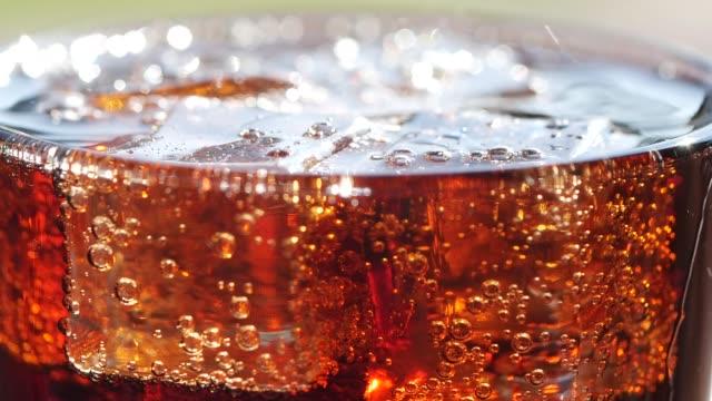 stockvideo's en b-roll-footage met sluit-omhoog een glas cola met ijsblokjes en bellen - hd format