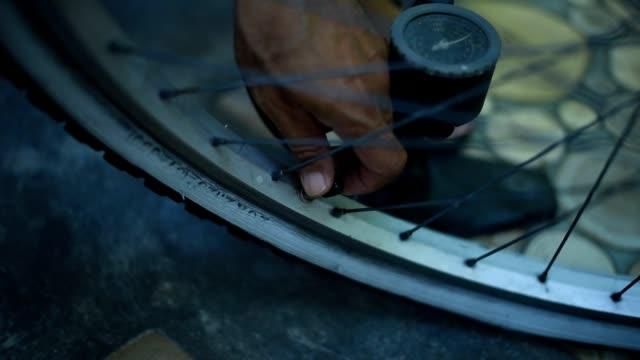 closeup a man inflating bike wheel, pumping air into the flat tire. - pneumatico video stock e b–roll