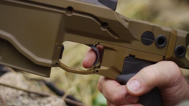Closeup a man's finger pulls the trigger of a rifle.