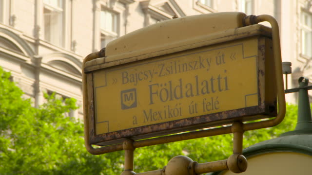 close-up: a yellow subway station sign in front of interesting architecture - budapest stock videos & royalty-free footage