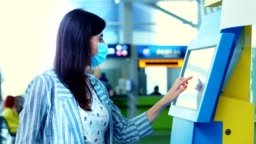 close-up, a young woman checks in on self check-in kiosk at the airport. air travel opening after coronavirus pandemic