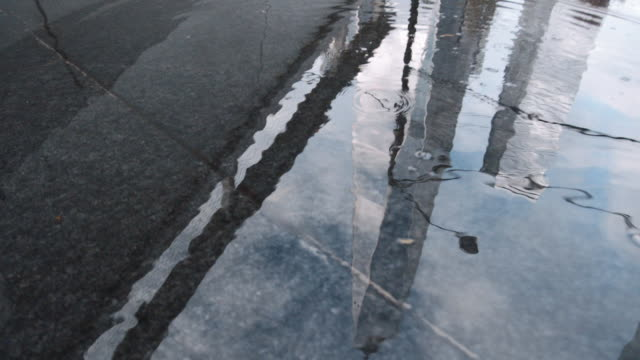 a closeup, abstract shot of an unrecognizable person walking through a puddle in front of nyc's world trade center - 水たまり点の映像素材/bロール