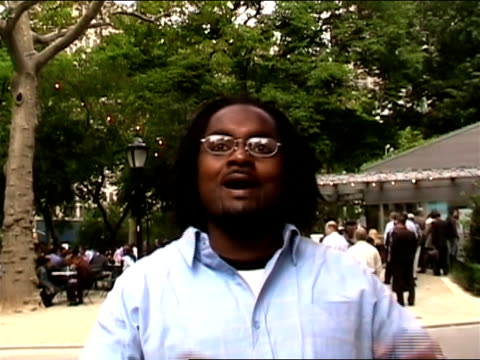 close-up, adult man with dreadlocks in public park removing eyeglasses showing eye-crossing trick/ new york city - 2006 stock videos & royalty-free footage