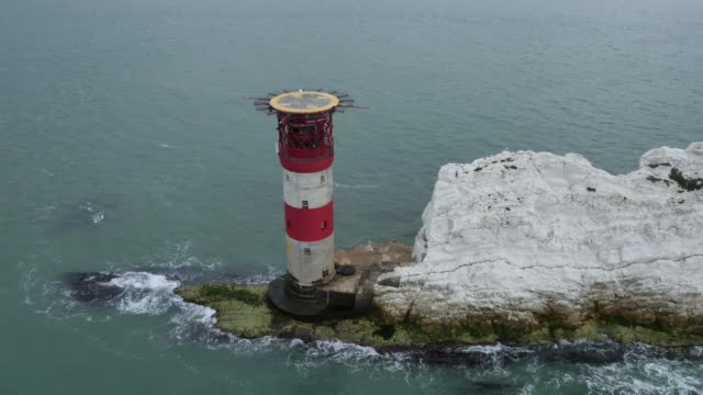Close-up aerial shot of the Needles Lighthouse (topped by its helipad) off the Isle of Wight, UK.