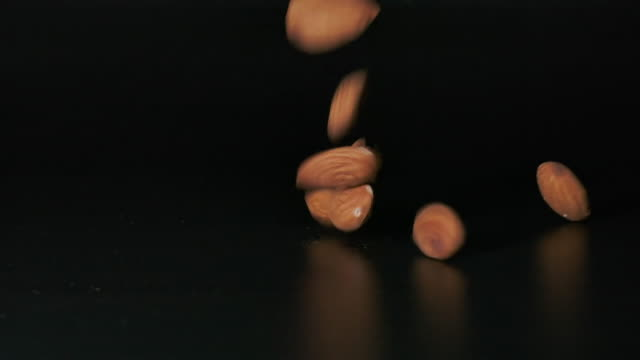 slo mo close-up almonds falling, shot with high speed camera - nut food stock videos & royalty-free footage