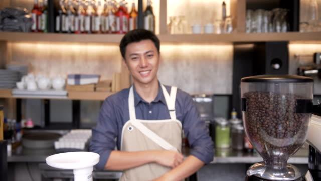 vídeos de stock, filmes e b-roll de foco e close-up vista frontal: young asian barista homem está sorrindo para ser dono de café café - barista