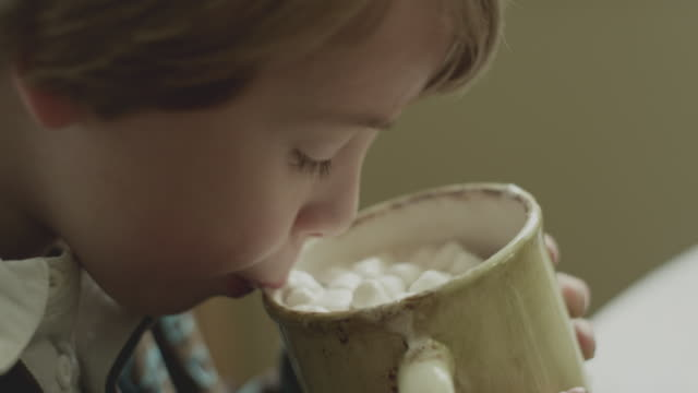 closeup as young boy enjoys hot cocoa - hot chocolate stock videos and b-roll footage
