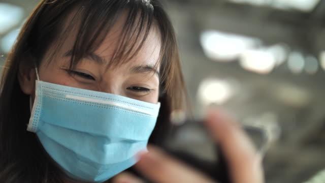 マスク付きスマートフォンを使用してクローズアップアジアの女性 - 安全衛生保護具 マスク点の映像素材/bロール
