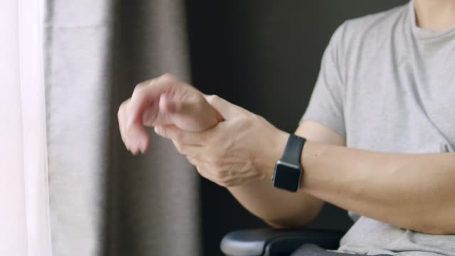close-up asian adult man having a hand pain.adult male massage on his hand while using laptop computer working from home. - rheumatism stock videos & royalty-free footage