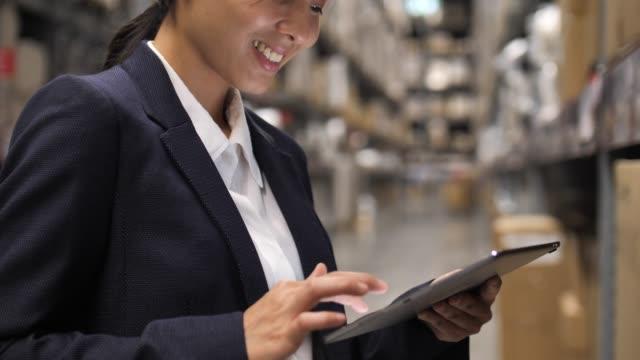 nahaufnahme asiatische geschäftsfrau mit digital tablet überprüfen die pakete in regalen im lager - industriegebäude stock-videos und b-roll-filmmaterial