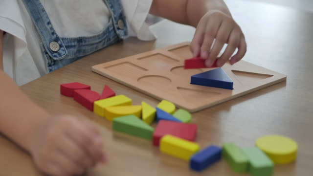 close-up, asian girls age 6-7 years kids playing with colorful wooden toy blocks staying home.homeschooling and distance learning - 6 7 years stock videos & royalty-free footage