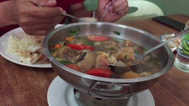クローズ アップ アジア男性がおいしいスパイシーな煮込みオックス テール スープを食べて - 煮込み料理点の映像素材/bロール