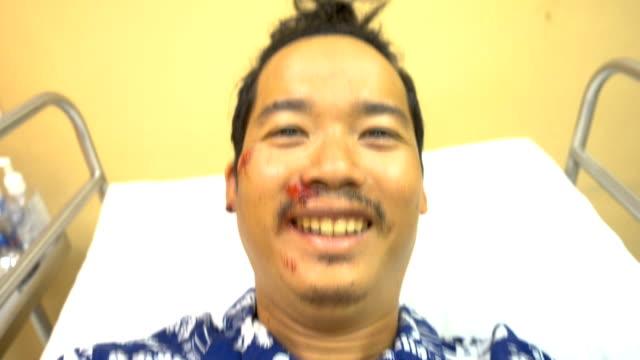 close-up asiatischer mann gesicht nach dem unfall auf dem bett im krankenhaus. - blauer fleck stock-videos und b-roll-filmmaterial