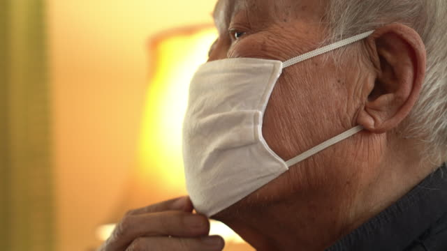 close-up asian man face wearing mask coughing at home - retirement community stock videos & royalty-free footage