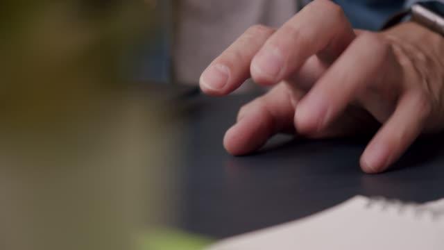 vidéos et rushes de gros plan main d'homme asiatique tapant son doigt sur la table tout en travaillant à la maison et l'abattage acte nerveux. - doigt humain