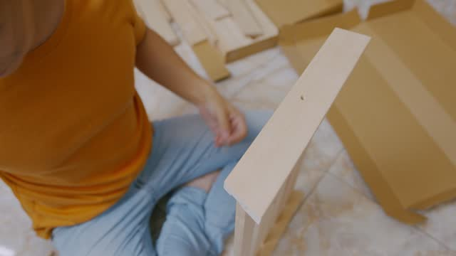 vídeos de stock e filmes b-roll de close-up asian man hands sitting on the floor doing  furniture assemble in the at home. - broca