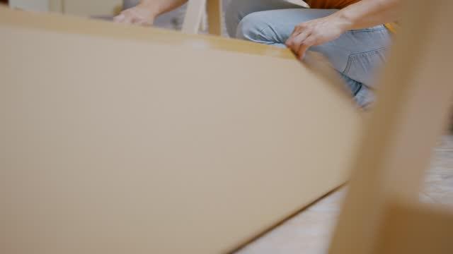 nahaufnahme asiatische mann hände sitzen auf dem boden öffnen eine möbelbox im haus. - werkzeug stock-videos und b-roll-filmmaterial