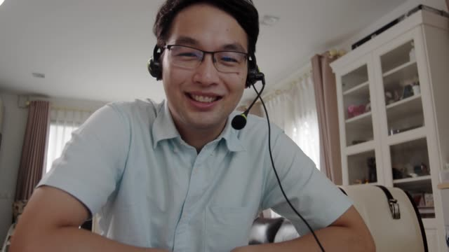 close-up asian man looking at camera and making video call conversation at home with smiling face. - speech stock videos & royalty-free footage