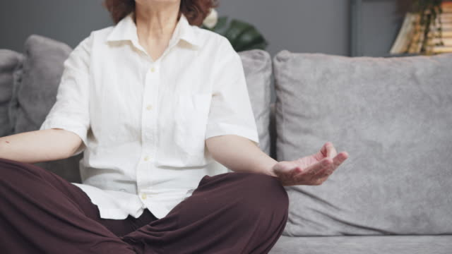close-up asian senior woman sitting and meditation in the lotus pose at home. mature woman sitting cross legged. retried and calm old female relieve stress by practicing yoga. focus training  or manage emotions - cross legged stock videos & royalty-free footage