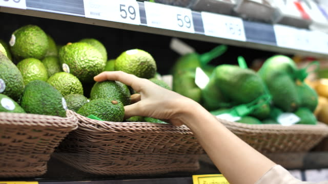 close-up asian woman avocado fruit shopping in supermarket - shelf stock videos & royalty-free footage