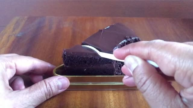 Close-up Asian woman eating delicious slice of chocolate cake