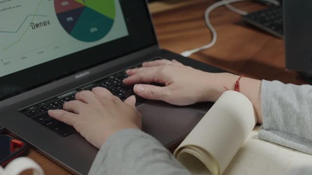 4k, närbild, asiatisk kvinna mänsklig hand medan kort anteckning och tryck på ett tangentbord laptop och smartphones som arbetar hemma, slow motion. - hot desking bildbanksvideor och videomaterial från bakom kulisserna