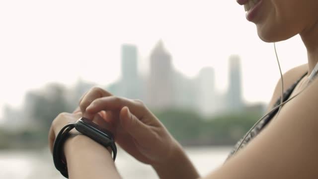 vídeos de stock e filmes b-roll de close-up asian woman using smart watch in the city - wireless technology