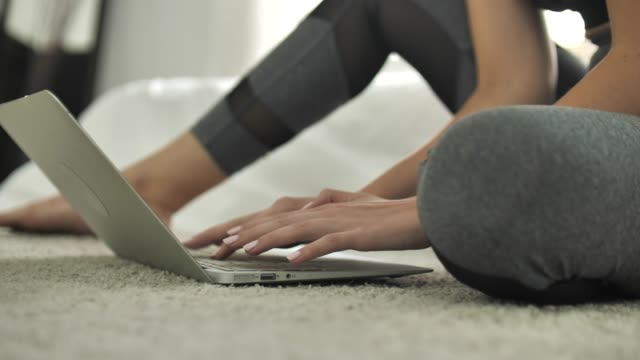 close-up athlete woman hand using laptop while sitting on floor at home - practising stock videos & royalty-free footage
