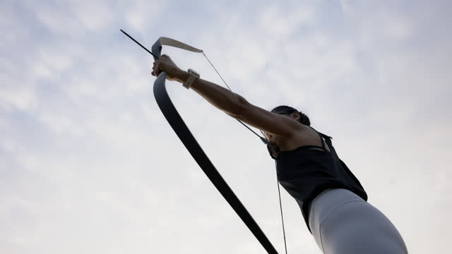 close-up attractive asian female practicing archery at the range . - heroes stock videos & royalty-free footage