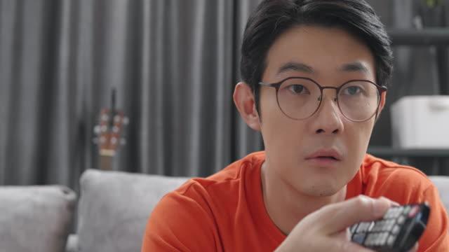 nahaufnahme attraktiver asiatischer mann sitzt auf einer couch und schaut zu hause im wohnzimmer fernsehen oder film zu sehen, während coronavirus quarantäne-sperrsituation. erwachsenen-wechselkanal mit fernbedienung. - fade in video transition stock-videos und b-roll-filmmaterial