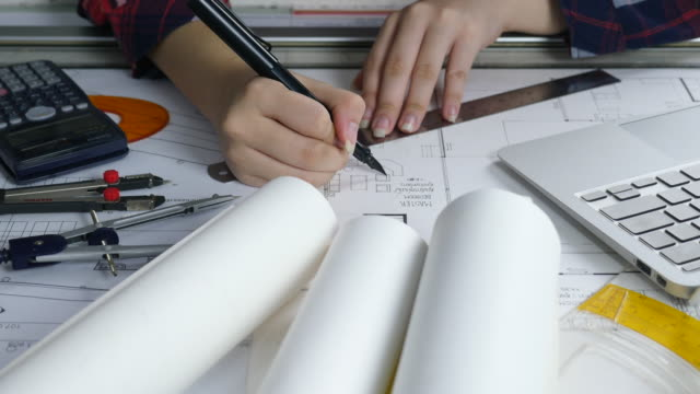 Close-up Attractive young female architect working at desk with plans on blueprint