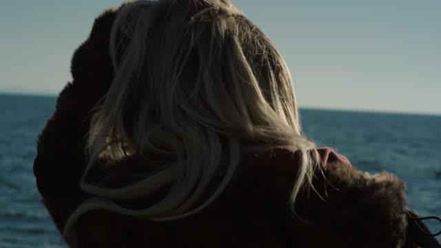 stockvideo's en b-roll-footage met close-up bach blond haarmeisje op de strand zonnige dagde wintertijd - sunny