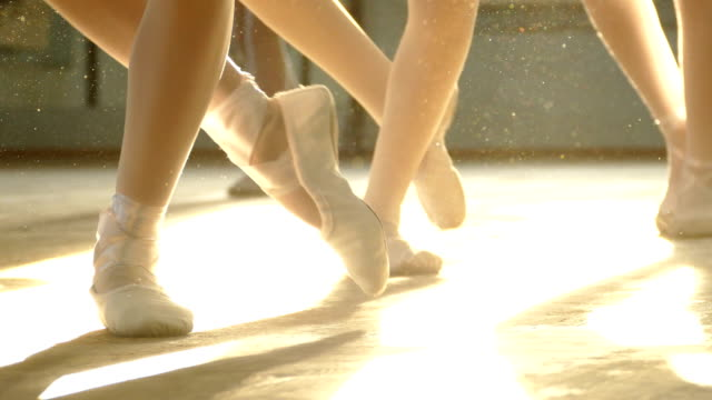stockvideo's en b-roll-footage met close-up-ballerina's voeten in de stralen van licht - balletdanser
