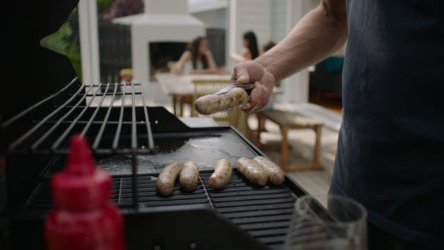 close-up barbecue with family in background - barbecue stock videos & royalty-free footage