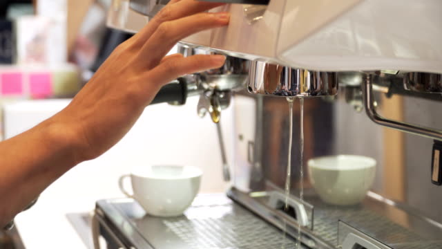 close-up: barista start making coffee by using coffee maker