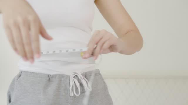 クローズアップ美しい肖像画若いアジアの体の女性ダイエット腰と腰を測定する薄い形状、アジアの女の子とスリムで測定テープ、減量とライフスタイルの概念。 - ほっそりした点の映像素材/bロール