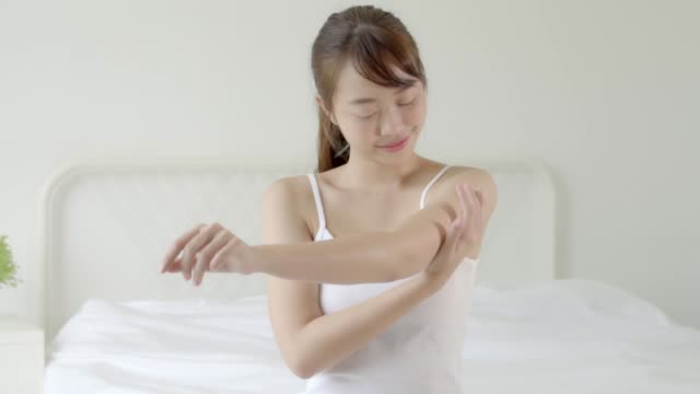 closeup beautiful young asian woman sitting on a bed stroking hand with soft smooth skin in the bedroom, girl applying body cream and lotion with treatment care, healthy and wellness concept. - human body part video stock e b–roll
