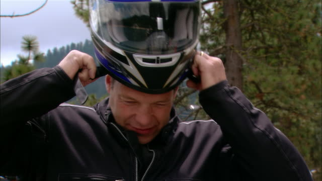 Close-up Biker putting on motorcycle helmet in Sierra National Forest / Fresno County, California, USA