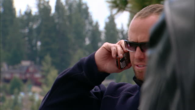 Close-up Biker talking on cell phone in Sierra National Forest / Fresno County, California, USA