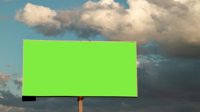 vidéos et rushes de panneau d'affichage de plan rapproché avec l'écran vert vide sur les nuages mobiles dans le fond de ciel dans le laps de temps - affiche