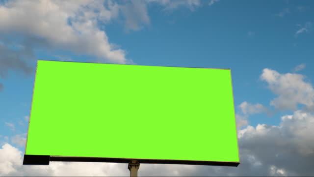 vidéos et rushes de panneau d'affichage de plan rapproché avec l'écran vert vide sur les nuages mobiles dans le fond de ciel dans le laps de temps - billboard