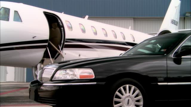 vidéos et rushes de close-up black car parking on runway near private jet outside hangar at opa locka airport/ miami, florida, usa - piste d'envol