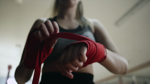 Close-up, boxer putting on hand wraps