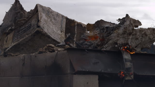 close-up burning debris drifts from a pile of rubble, including a smashed air conditioner, after a structure fire - myrtle creek stock videos & royalty-free footage