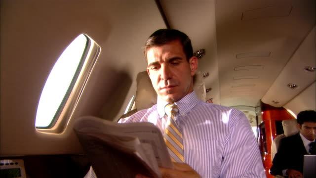 Close-up Businessman reading newspaper on private jet/ Miami, Florida, USA