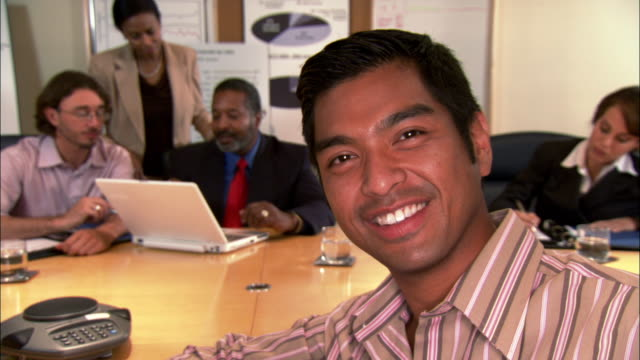 close-up businessman smiling near colleagues using laptop in conference room - goatee stock videos & royalty-free footage