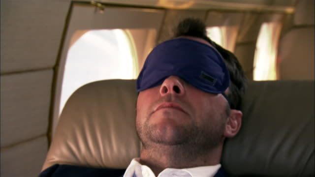 stockvideo's en b-roll-footage met close-up businessman wearing sleep mask and reclining in private airplane - zakenreis